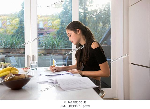 Caucasian girl doing homework in domestic kitchen