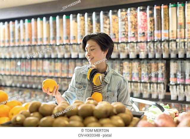 Young woman with headphones grocery shopping, holding orange in market