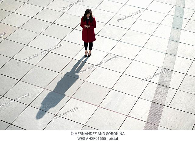 Businesswoman using smartphone and standing on concrete floor