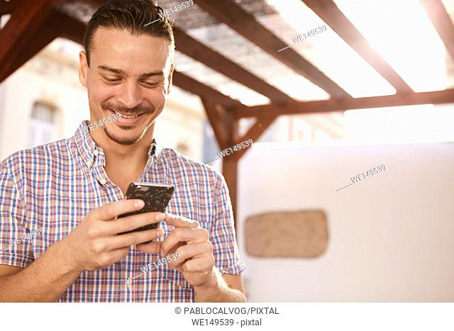 Cute dark haired guy grinning from ear to ear with satisfaction while looking at his cellphone that he is holding with both hands