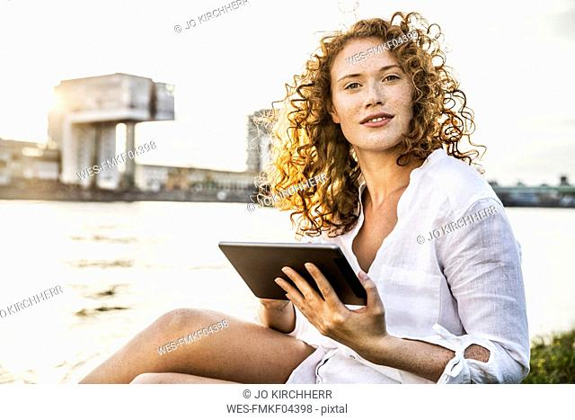 Germany, Cologne, portrait of young woman with tablet sitting at riverside