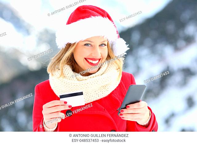 Happy girl on christmas wearing santa claus hat holding credit card and smart phone with a snowy mountain in the background