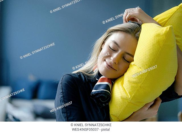 Portrait of smiling young stewardess with yellow pillow