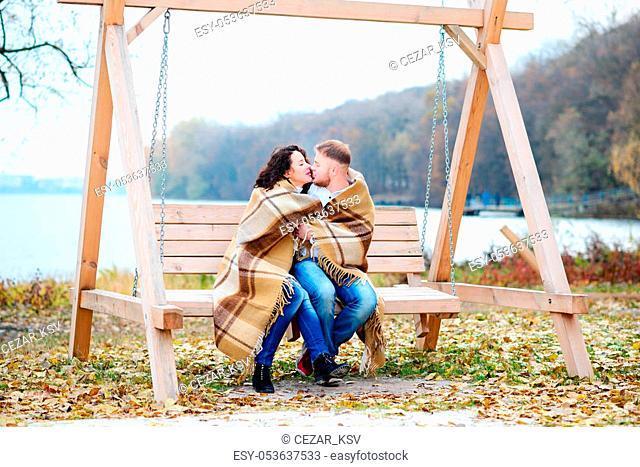 Amorous couple on romantic date on swings outdoor, autumn