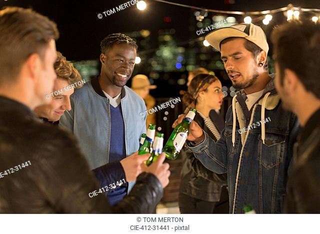 Young adult friends toasting beer bottles at rooftop party