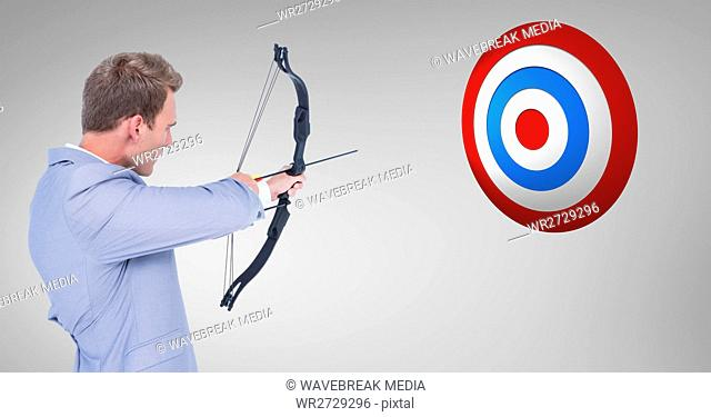 Digital composite image of businessman aiming at the target board