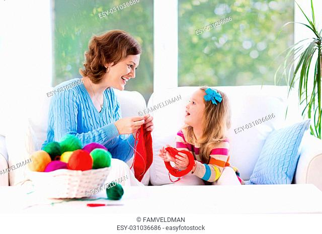 Mother and daughter knitting woolen scarf. Mom teaching child to knit. Crafts and hobby for parents and kids. Toddler girl kid with wool yarn in a basket