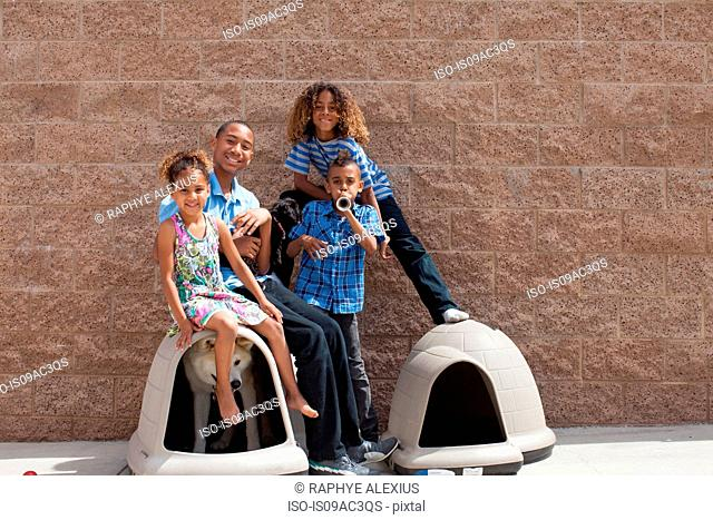 Portrait of four siblings and dog in kennel