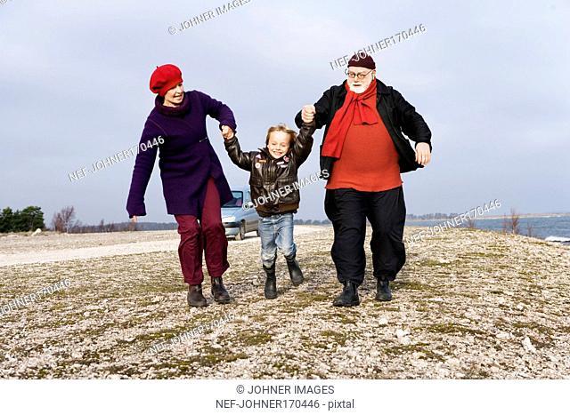 A man, a woman and a boy running on a beach holding hands