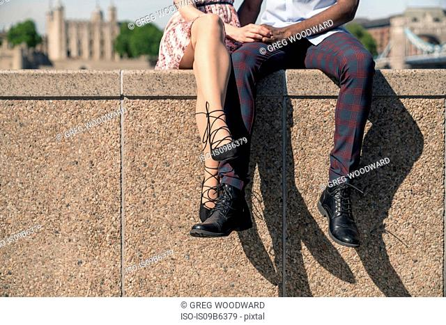 Young couple sitting on wall, holding hands, low section