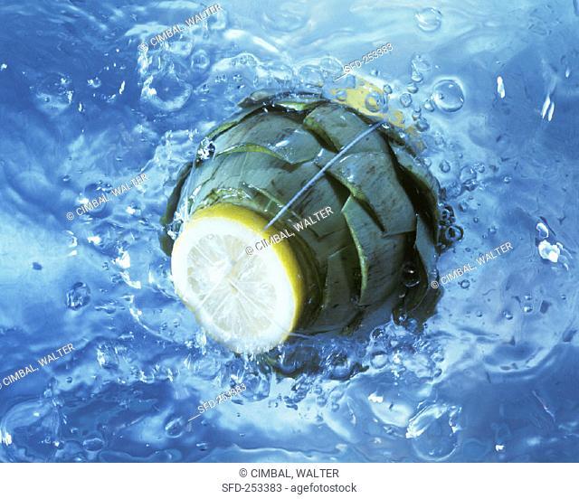 Artichoke with slice of lemon in boiling water