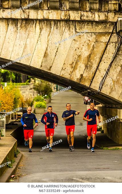 Group of men jogging along the banks of the River Seine, near Pont de la Concorde, Paris, France