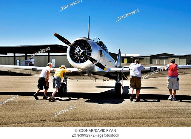 North American AT-6 trainer aircraft being pushed into position for taxiing at the Warhawk Museum at the Nampa Municipal airport