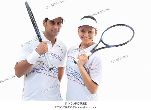 Portrait of male and female tennis players holding rackets isolated over white background