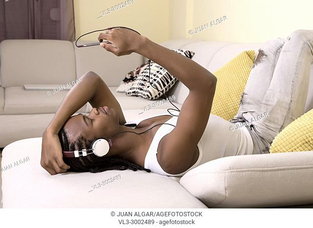 Young black man lying on sofa and enjoying the music with smartphone