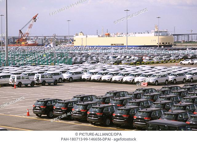 09 July 2018, China, Guangzhou: New Jeep vehicles (r) in a parking lot in the Nansha free trade zone at the port. In the background is a CSC RoRo Logistics car...
