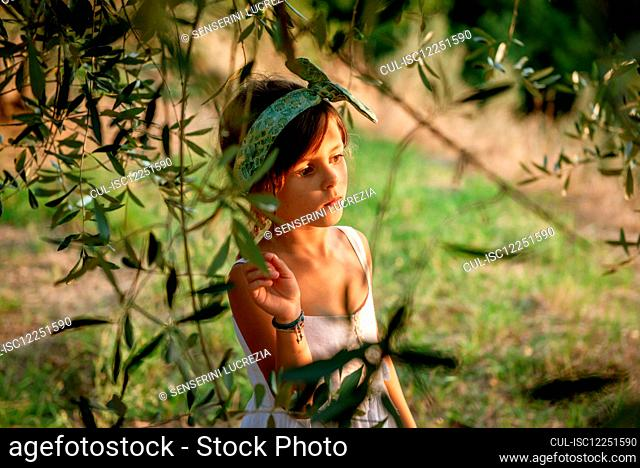Portrait of girl wearing white summer dress standing under an olive tree in garden
