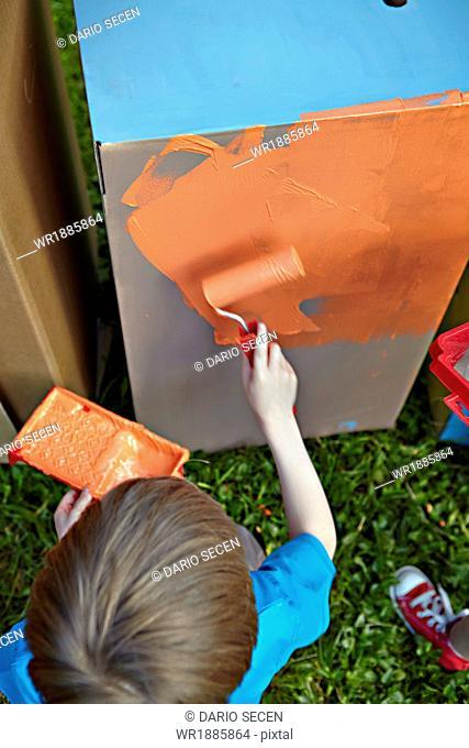 Boy painting cardboard box, Munich, Bavaria, Germany