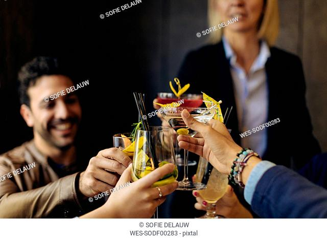 Colleagues toasting with cocktails in a bar