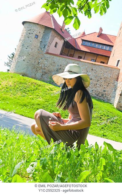Teen girl picking flowers near old castle