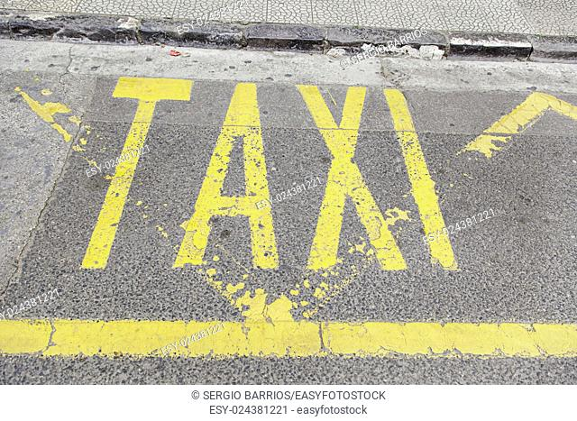Taxi sign on asphalt, detail of a traffic signal, information and tansporte