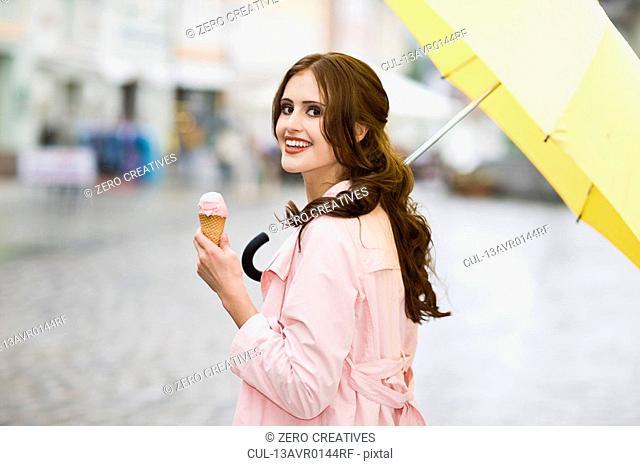 girl enjoying icecream in the rain