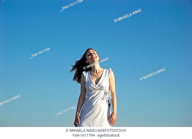 Portrait of a smiling young woman wearing summer dress against blue sky