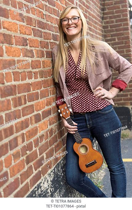 Woman standing against brick wall with ukulele