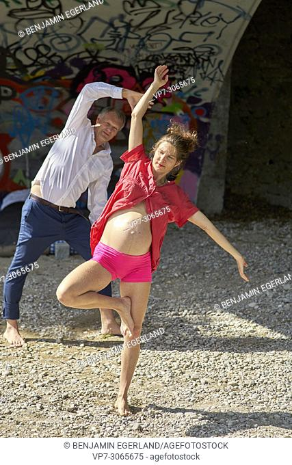 Couple, pregnancy, exercising, healthy lifestyle. At river Isar, Munich, Germany