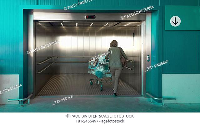 Woman with shopping cart entering an elevator, Barcelona, Spain