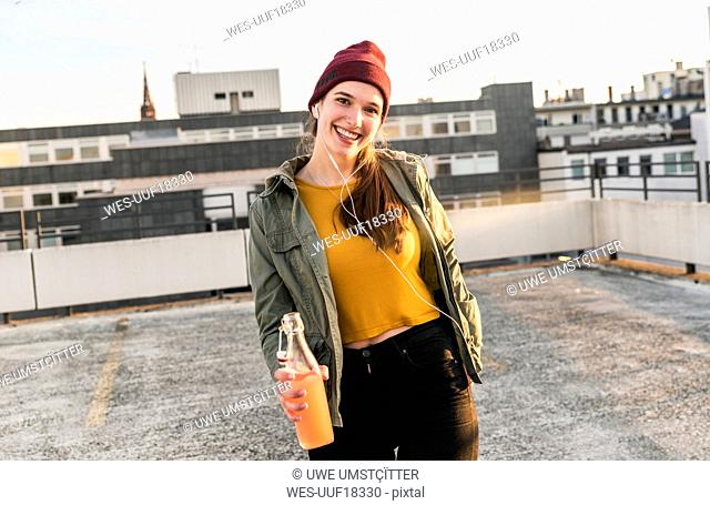 Portrait of happy young woman with earphones and drink on parking deck