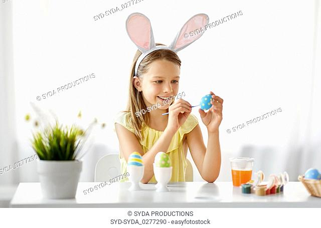 happy girl coloring easter eggs at home