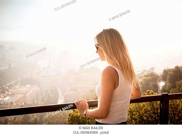 Woman on balcony looking at elevated view of Malaga, Spain