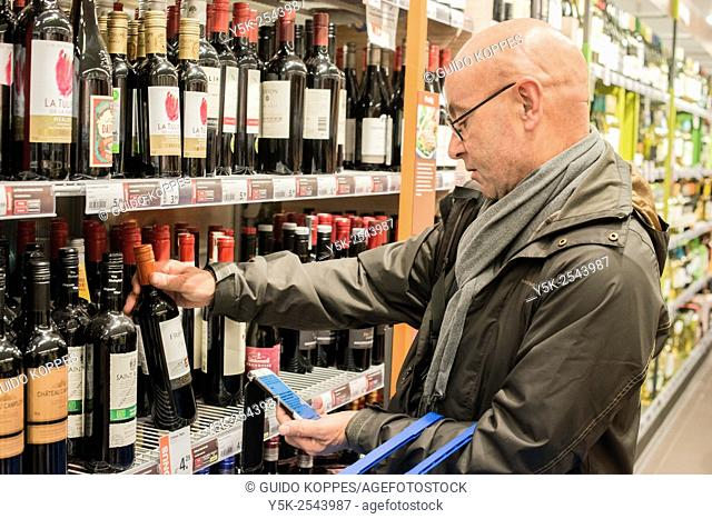 Rotterdam, Netherlands. Middle aged bald male choosing a bottle of wine in the supermarket while comparing it to information on his smartphone