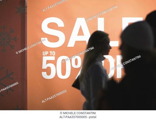Poster proclaiming 'Sale up to 50 off' and shoppers silhouetted in foreground