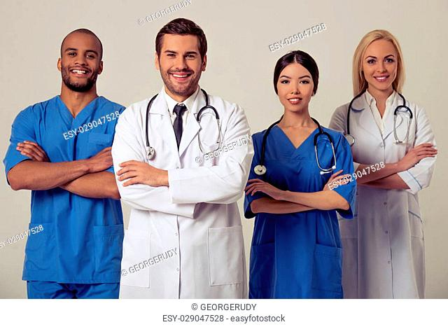 Group of medical doctors of different nationalities and genders is looking at camera and smiling, standing with crossed arms on gray background