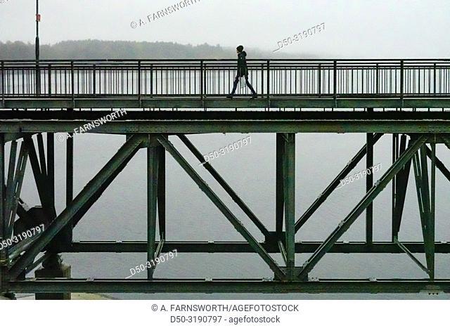 Stockholm, Sweden A pedestrian walks over the Lidingo bridge in the morning fog