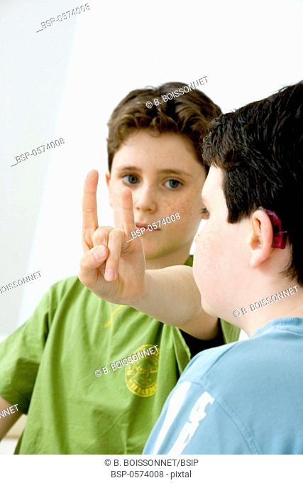 SIGN LANGUAGE Models. Do not use for HIV. Young boy using the French sign language to discuss with his hearing-impaired brother