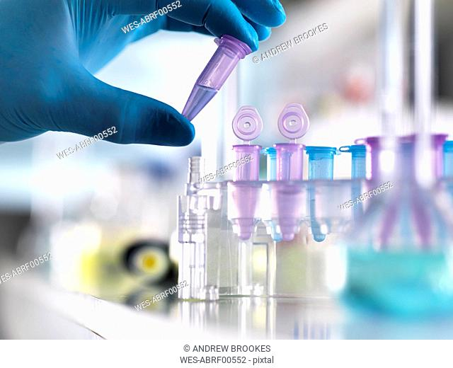 Cropped hand of male scientist holding DNA samples in vial at laboratory