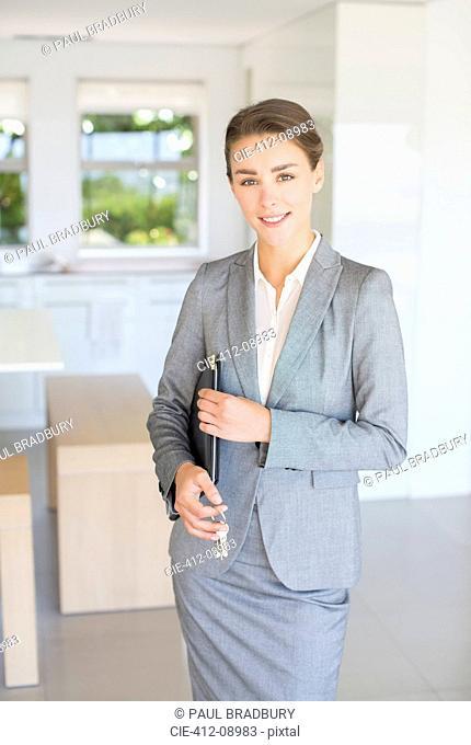 Portrait of confident realtor holding house keys