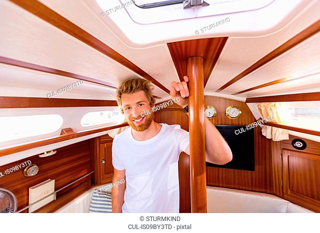 Young man in sailboat cabin, portrait