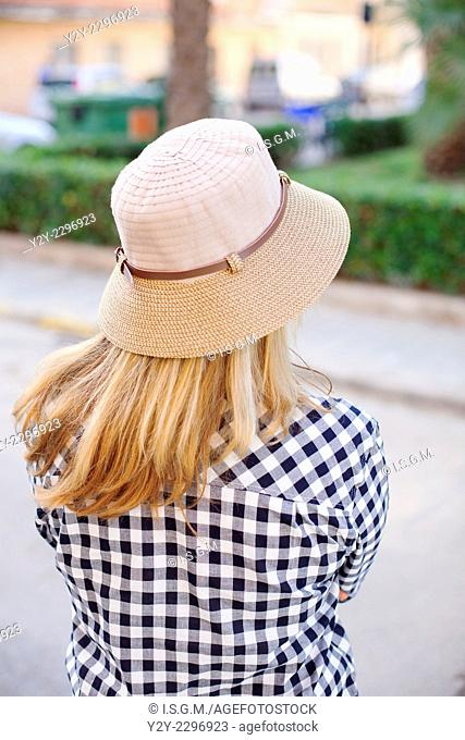 Woman waiting in the street with hat