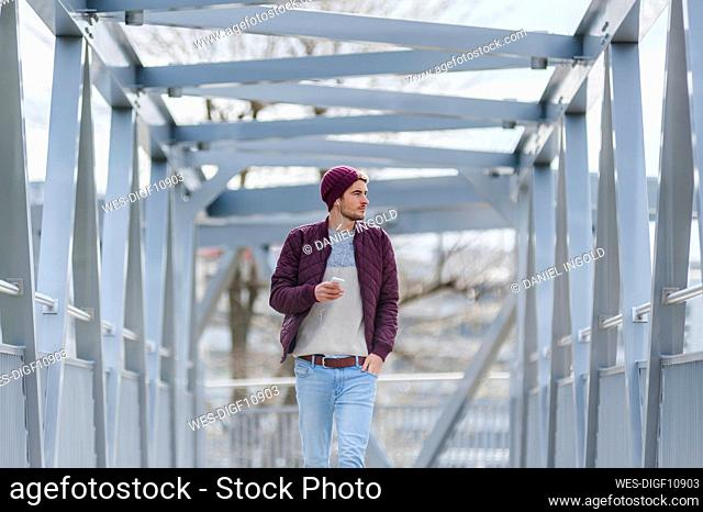 Young man walking on a bridge with earbuds and smartphone