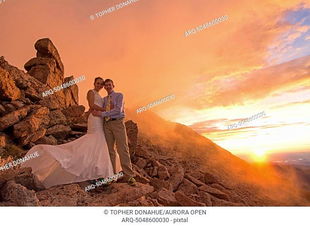 A couple shows off their wedding spirit on a 14.000 foot mountain