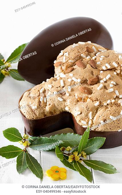 Colomba pasquale, typical italian sweet for Easter and chocolate egg on white wooden background