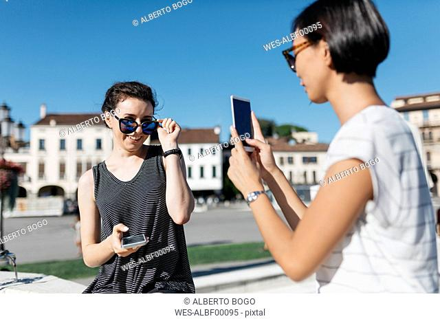 Italy, Padua, young woman taking picture of her friend with smartphone