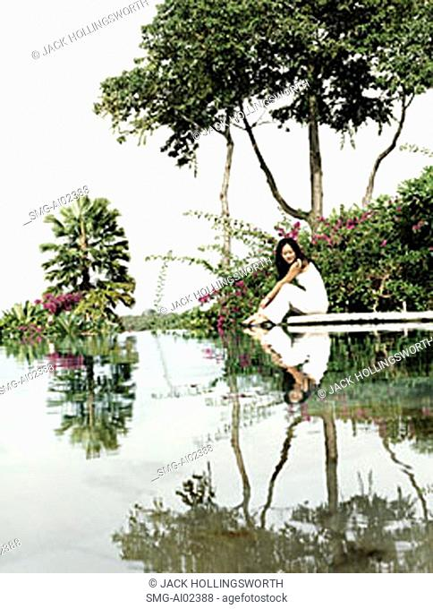 Woman sitting on water's edge with trees with reflection