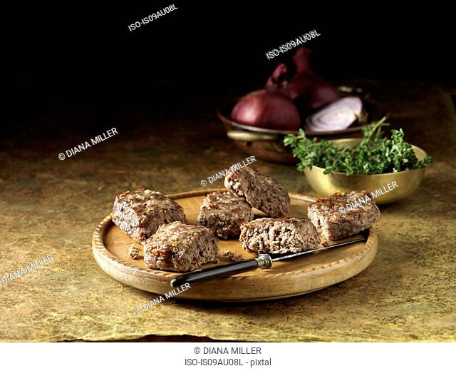 Venison with roasted red onion stuffing on rustic chopping board