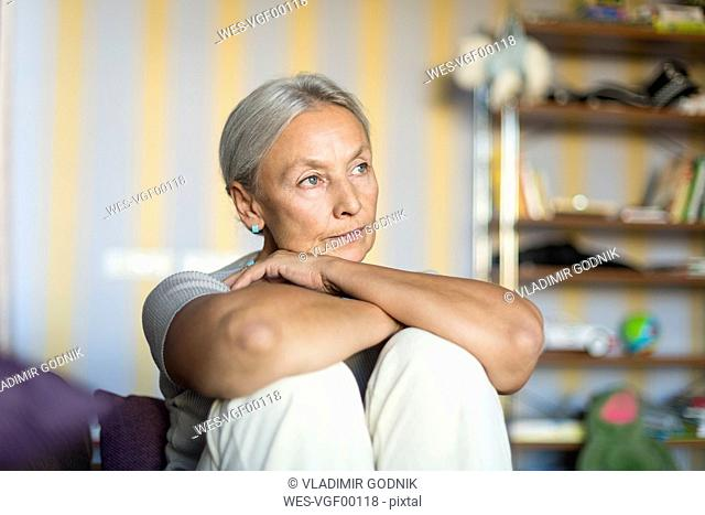 Portrait of pensive senior woman sitting on the couch at home