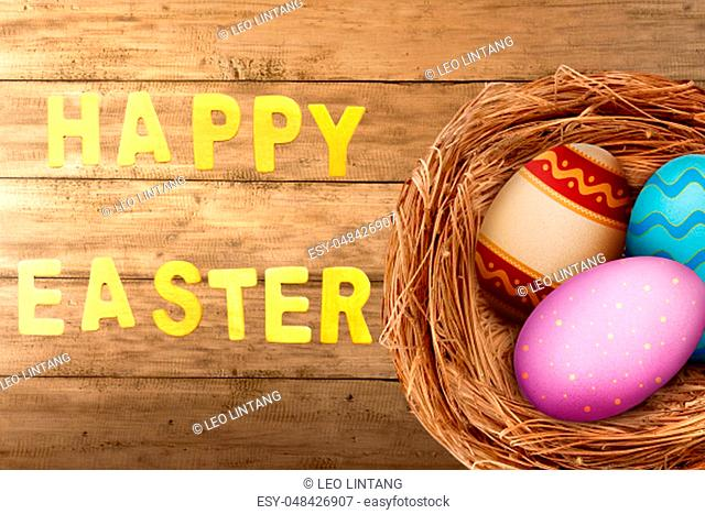 Colorful easter eggs in the nest on wooden table with happy easter greeting. Happy Easter